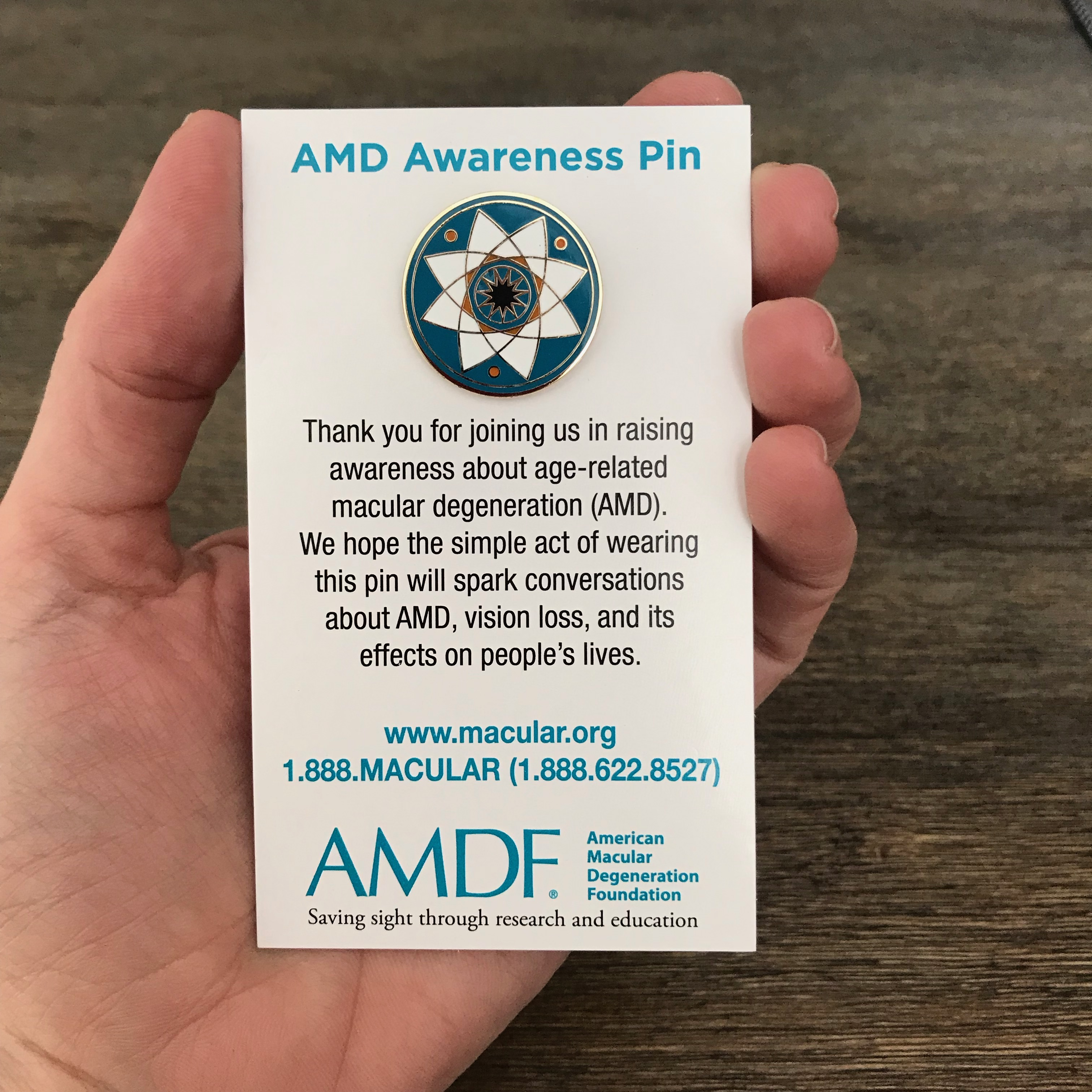 Age-related macular degeneration awareness pin mounted on backing card.